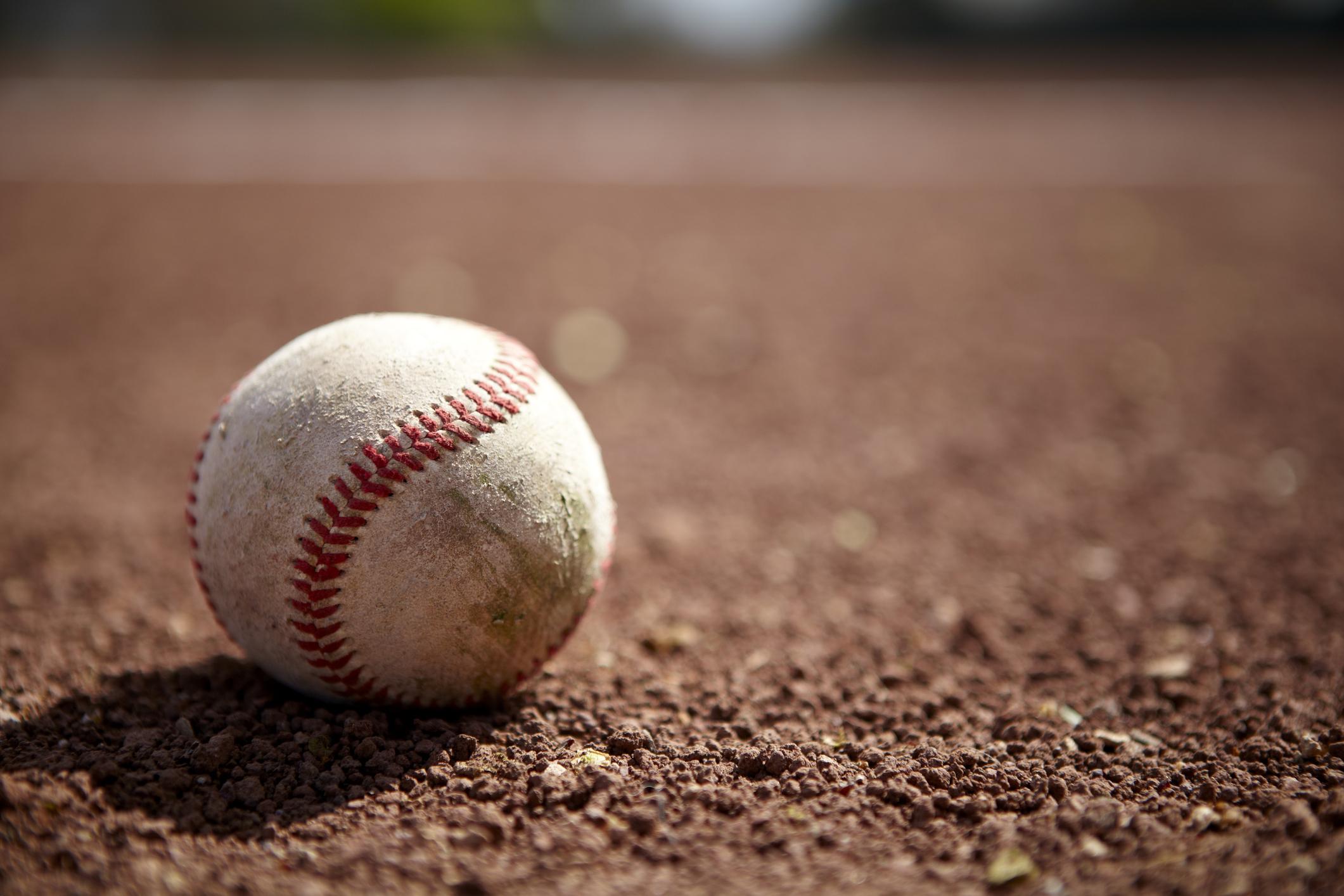 Still life of a baseball on baseball diamond