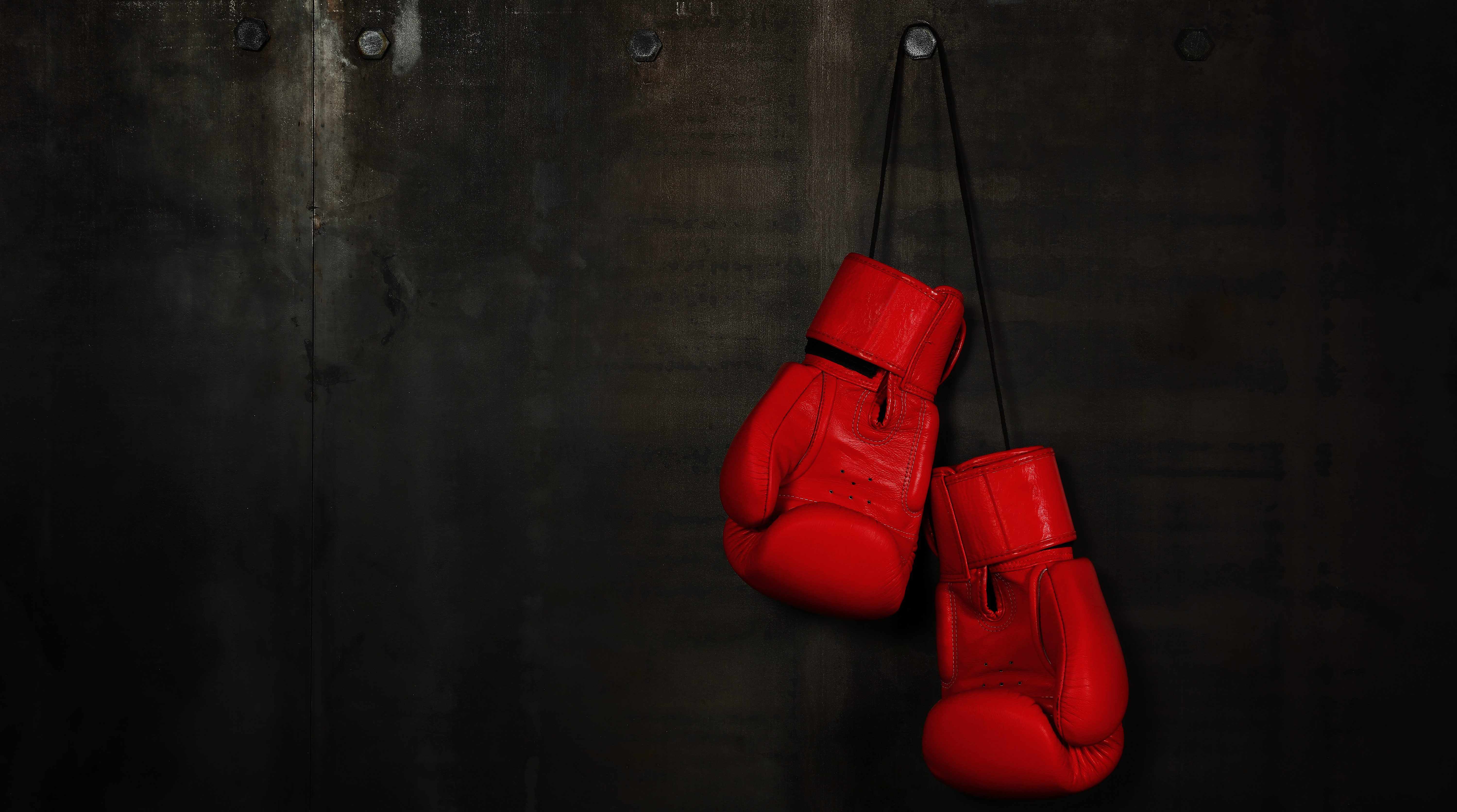 Close-Up Of Red Boxing Gloves Hanging On Wall